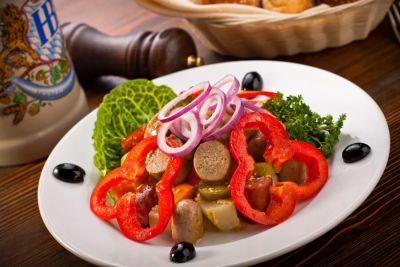 Наш фирменный салат с немецкими колбасками, сыром, красным луком, маринованным огурчиком под горчичной заправкой