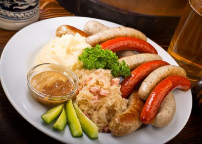 Ассорти колбасок. Подается с картофельным пюре, маринованными огурцами и немецкой горчицей